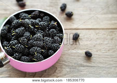 Fresh mulberry berries in a saucepan. Preparation of jam from mulberry. Top view space for text