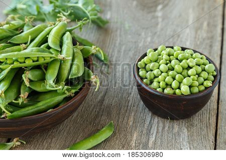 young peas in a clay plate on a wooden table. next to a plate are a pea pods.