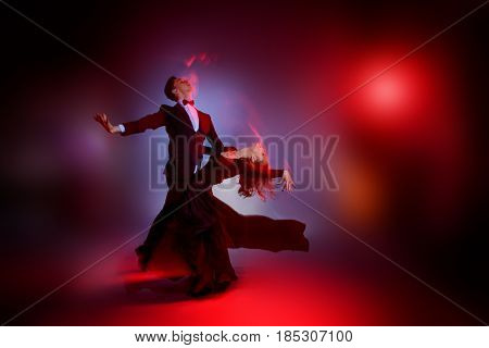 Art concept. Beautiful vigorous dancers performing tango at studio.