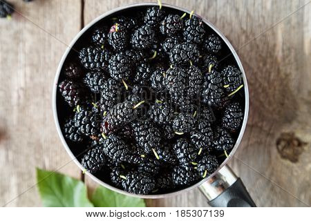 black mulberry berries in a pink pot on a wooden table. in the foreground are mulberry berries and sprig with ripened berries. top view