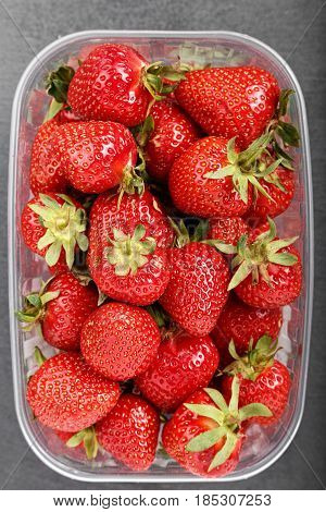 Ripe strawberry in a plastic box on a black background top view