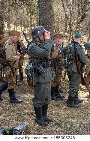 Gatchina, Russia - May 7, 2017: Historical reconstruction of the battles of World War II. Soviet and German soldiers before the battle. A German soldier looks through binoculars.