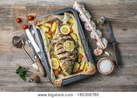 Appetizing baked fish, covered with juicy lemons, garlic and salt on side, topview
