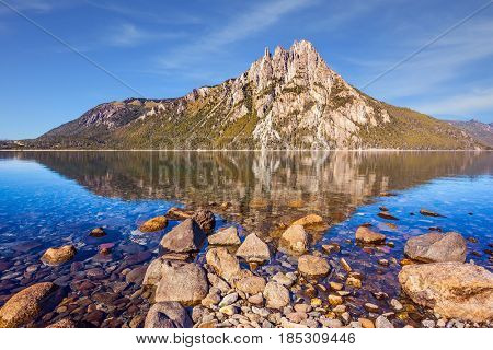 The mirror water of shallow lake reflects sharp rocks. Picturesque mountain in San Carlos de Bariloche, Argentina. The concept of exotic and extreme tourism
