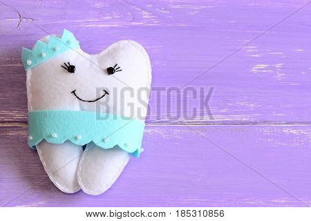 Felt tooth fairy pillow isolated on wooden background with copy space for text. Handmade children's felt tooth fairy pillow. Stuffed toy crafts idea. Top view. Closeup