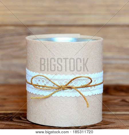 Recycled tin can isolated on wooden background. Decorative tin can crafts. Easy and cheap way to make crafts for home. Recycling tin can into organizer for stationery. Closeup