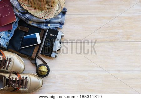Top view of traveler´s accessories: leather bag blue jeans hat check shirt gold sneakers smart phone vintage camera and passport on wooden background with space for text. Travel outfit concept.