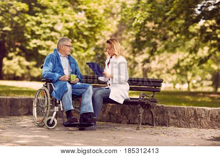 nurse checking up the history of the disease senior patient in wheelchair