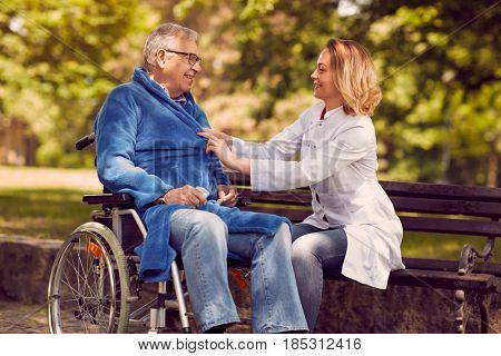 Smiling caregiver nurse helping disabled senior patient in wheelchair