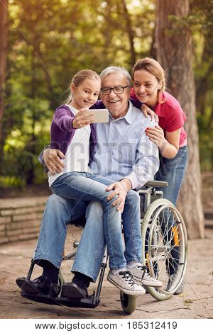 family selfie time in the park - granddaughter, daughter and disabled man in wheelchair