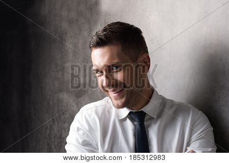 Shy smile. Portrait of youthful businessman with stubble. He is looking at camera timidly