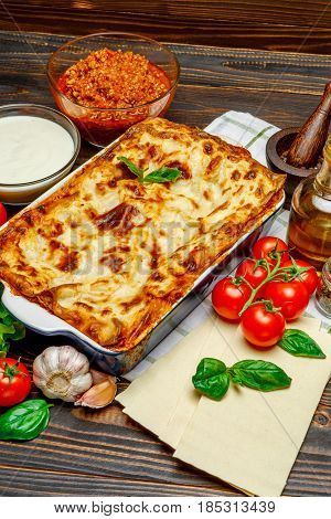 Classic Lasagna with bolognese and bechamel sauce on wooden table