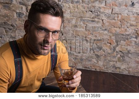 Cheers. Portrait of stylish man with glass of whiskey. He looking at camera with gentle smile