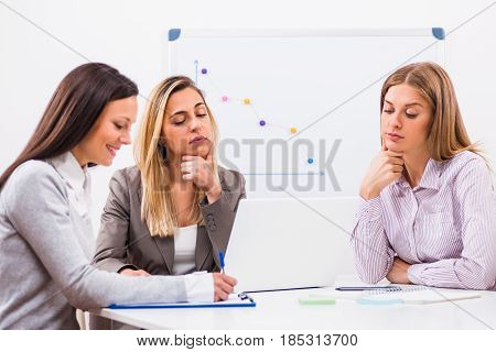 Three businesswomen are having meeting in their office.