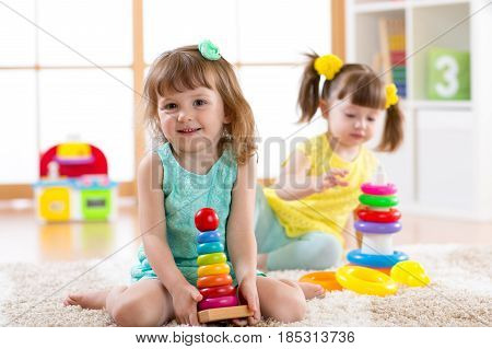 Children play together. Educational toys for preschool and kindergarten kids. Little girls build pyramid toys at home or daycare.