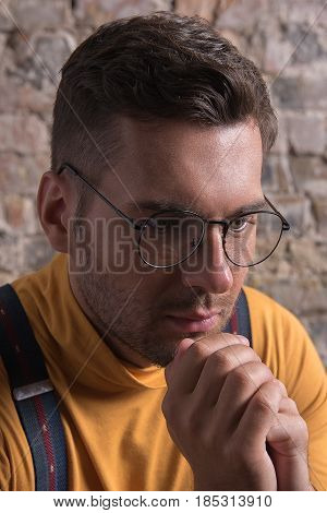 Keep calm. Portrait of lonely young man clasping of hands and looking down. He is sitting against brick wall