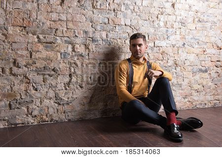 Stylish and confident. Elegant guy in interior with brick wall sitting on wooden floor. He looking at camera dreamy. Copy space