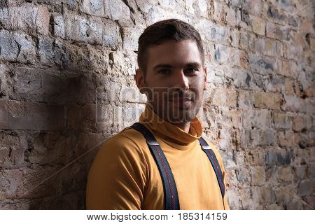 Good mood. Stylish young male looking at camera joyfully. He wearing orange polo neck
