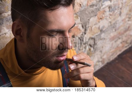 Feeling empty. Close up portrait of thoughtful lonely man with closing eyes. He smoking and thinking about life