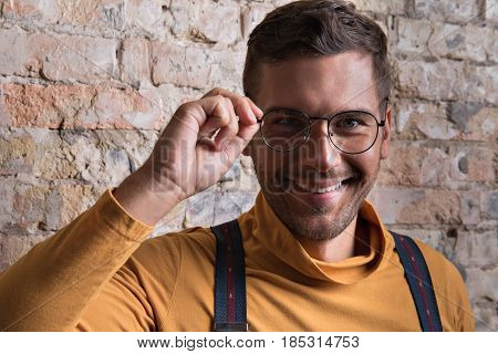 I see you. Portrait of stylish guy looking at camera with gladness. He touching his glasses and smiling