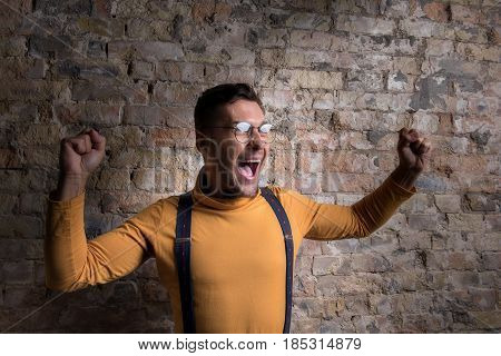 I am winner. Young man celebrating his success with arms up. He looking aside with happiness