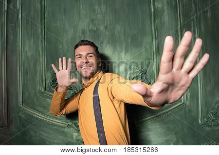 Full of energy. Stylish bearded male saying hello by one hand and stretching arm to camera. Focus on palm
