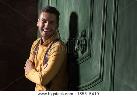 You make my day. Happy male posing with smile leaning against green wall. His arms are crossed. He looking at camera joyfully