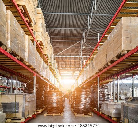 Warehouse transport and freight company. In the foreground a pile of cardboard boxes and a coil of plastic tubing. Bright sunlight.