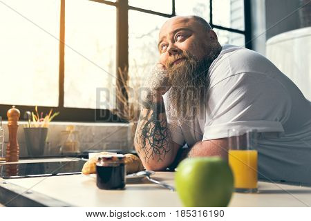 I wish I could eat something delicious right now. Dreamful fat guy is standing in cook room and looking up pensively. Healthy breakfast on table
