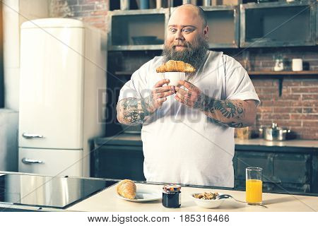 I will eat it right now. Hungry male fatso is holding cup with croissant on it and looking at food with appetite. He is standing in kitchen near table