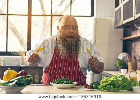 Cooking is my passion. Portrait of excited fat man is ready to mix salad before eating. He is holding spoons and looking at camera with hunger