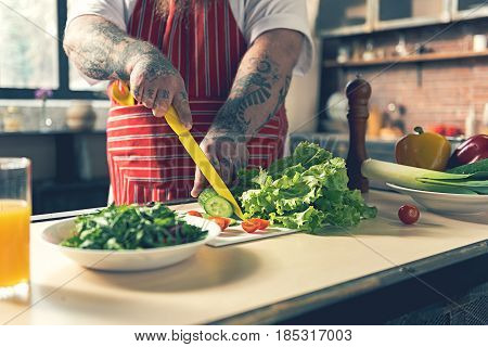 Close up of tattooed male arms cutting cucumber for salad. Thick chef is standing at table in kitchen
