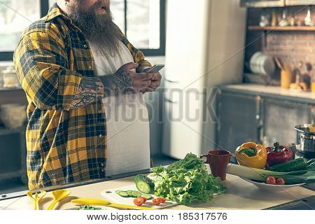 Cheerful fat man is typing message on smartphone while standing in kitchen. Fresh vegetables on table