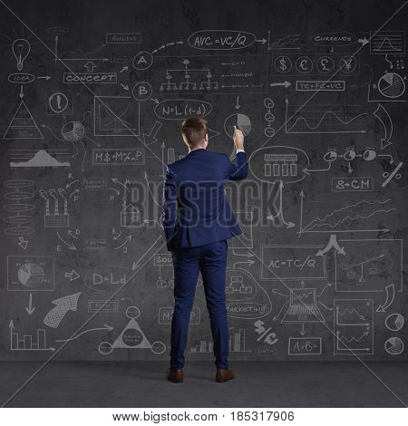 Businessman standing and drawing schemes. Business and office, concept.