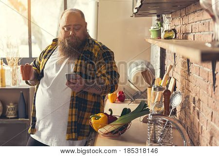Lazy thick guy is using mobile phone while drinking coffee in kitchen. He is standing in kitchen with relaxation