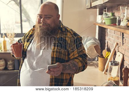 Portrait of happy fat man enjoying tea in kitchen. He is messaging on smartphone and smiling