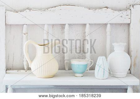 the white dinnerware on white wooden shelf