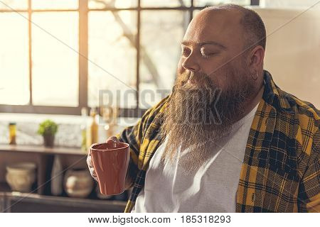 What can be better coffee in the morning. Relaxed fat man is holding cup and enjoying coffee smell. His eyes are closed with pleasure