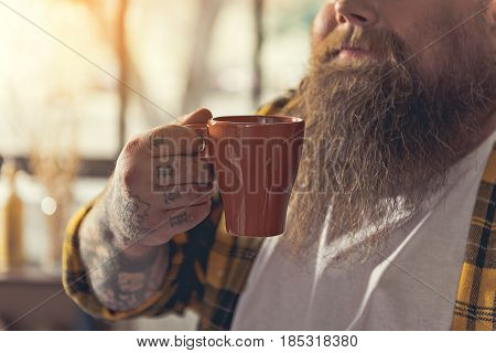 Close up of male arm with tattoo holding cup of coffee. Bearded fat man standing and smiling