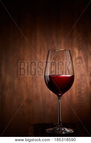 Half-full fragile wineglass of red wine standing on a wooden background. Brightly tasty wine. Luxury lifestyle and celebration. Natural drink. Viticulture, grapes and winery. Vertical photo.