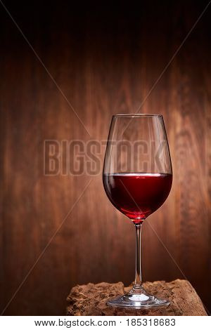 Red wine in the pure elegant wineglass standing on a wooden stand against wooden background. Natural material and product. Luxury lifestyle. Sommelier and tasting. Viticulture, grapes and winery. Vertical photo.