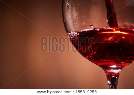 Close-up of brightly red wine poured in the wineglass and abstract splashing against brown background. Macro and horizontal photo. Luxury lifestyle. Still-life and background. Sommelier and degustation.