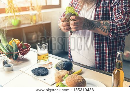 Close up of male hands holding appetite burger. Fat man is standing near table with glass of beer and vegetables on it