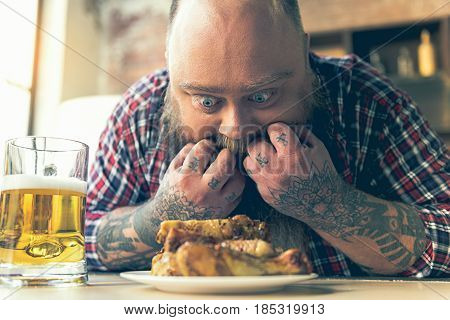Starving male fatso is looking at fried chicken legs with desire. He is licking his fingers
