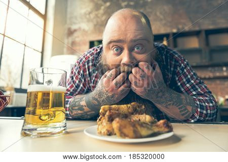 I want it right now. Hungry thick bearded guy is crazy about unhealthy food. He is looking at camera with temptation while putting fingers into mouth. Glass of bear and meat on table