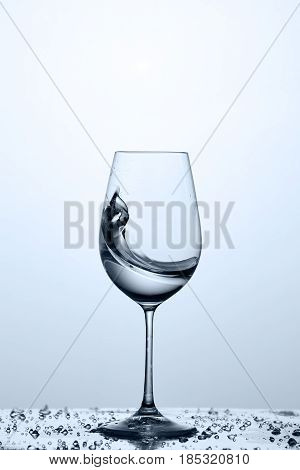 Splashing transparent water wave in the wine glass while standing on the glass with water bubbles against light background. Drinking and useful water. Care for the environment. Concept of the healthy lifestyle.