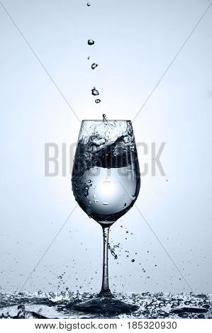 Bubbles of drinking water falling in the wineglass standing on the glass with droplets against light background. Pure and clear water. Environmentally friendly product. Care for the environment and health. Healthy lifestyle.