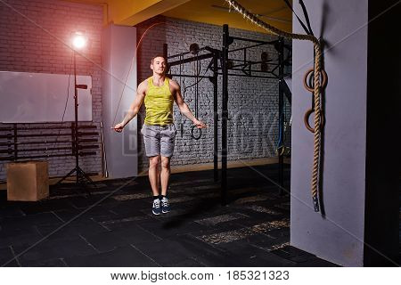 Athlete man in the sportwear using jump ropes for the workout in a cross-training gym. Sportsman in the t-shirt, shorts and sportive shoes. Healthy lifestyle.