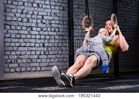 Young athlete father and little cute son exercising with gimnastic rings and smiling against brick wall in the gym. Fathet and son in the sportwear and sportive shoes. Happy family. Rearing children in the healthy lifestyle.