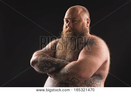 Waist up portrait of serious fat naked bearded man standing with crossed arms. He has tattoo over all his body. Isolated and copy space